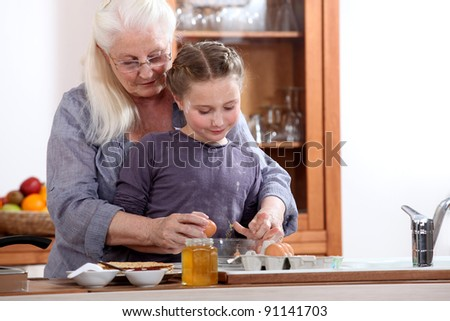 Little girl cooking with grandmother - stock photo