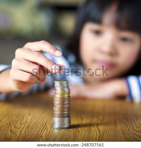 Little girl counts his coins on a table, Select focus at coins - stock photo