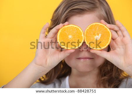 Little girl covering eyes with slices of orange - stock photo