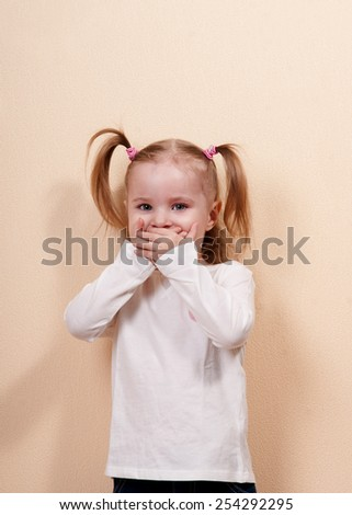 Little girl covering her mouth by hands, indoors vertical shot - stock photo
