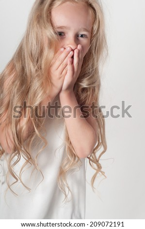 Little girl covers her mouth with her palms - stock photo