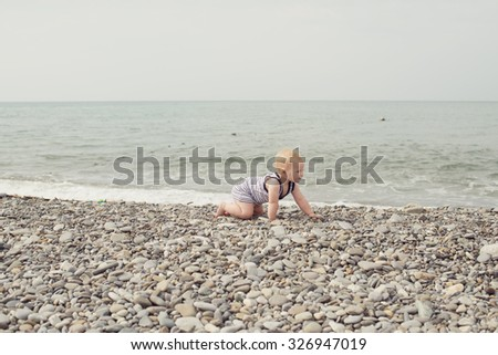 Little girl crawling on the sea beach - stock photo