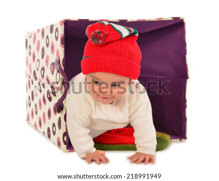 Little girl crawling out of a basket. - stock photo