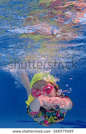 little girl creates bubbles under water in the pool  - stock photo