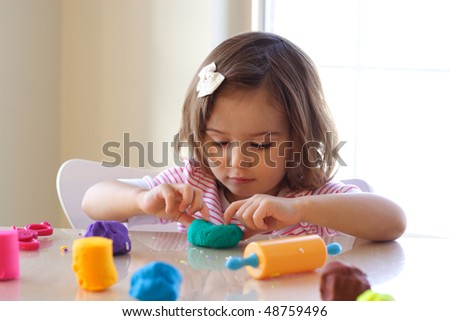 Little girl creating toys from play dough - stock photo