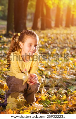 Little girl crouch in the autumn park, looking away,Sunset light, shallow doff, lens flare - stock photo