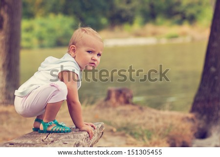 Little girl crouching on the bench - stock photo