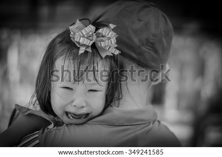 Little girl crying between stranger holding ,black and white col - stock photo