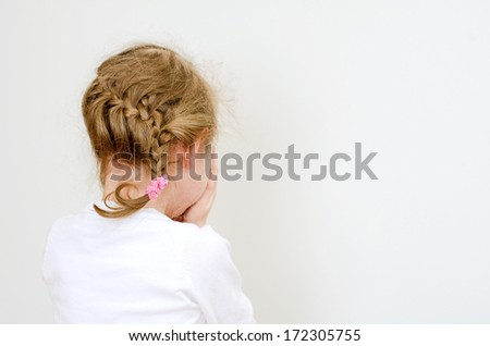 Little girl crying in the corner. - stock photo