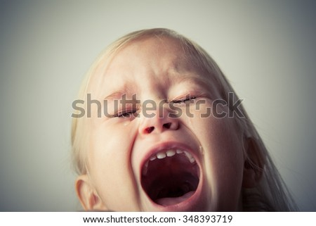 Little girl crying. Shouting. Really upset. Tears on her face - stock photo