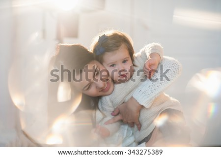 Little girl cuddling with her mother in a nice winter clothes, baby, lifestyle, childhood, joy, family values, life style - stock photo