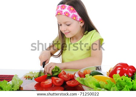 little girl cut fresh tomatoes. Isolated on white background - stock photo