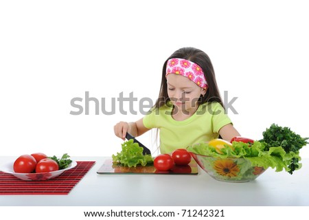 Little girl cut salad at the table. Isolated on white background - stock photo