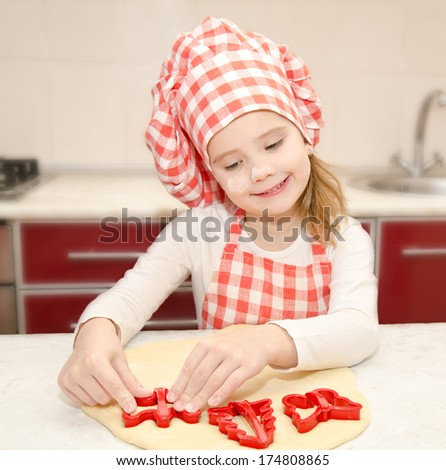 Little girl cuts dough with form for cookies in the kitchen - stock photo