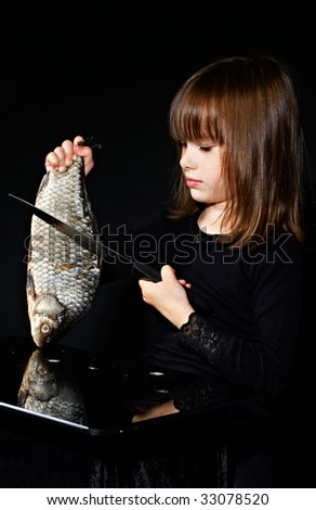 little girl cuts raw fish - stock photo