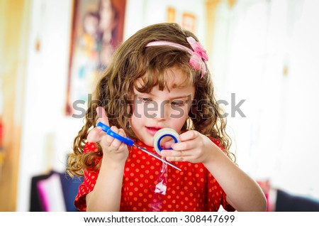 Little girl cutting adhesive tape making crafts - stock photo