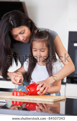 Little girl cutting pepper with the help of her mother - stock photo