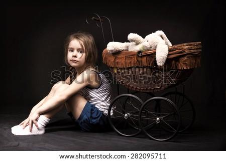 little girl dark background stroller dress bow - stock photo