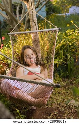little girl daydreaming in a hammock in backyard - stock photo