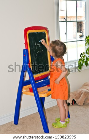little girl decides home arithmetic example on the blackboard