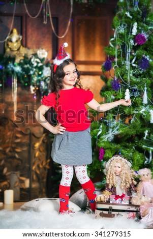 little girl decorates Christmas tree for Xmas - stock photo