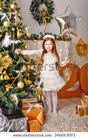 Little girl decorates the Christmas tree. Girl holding a balloon. Holiday and fun. 2017