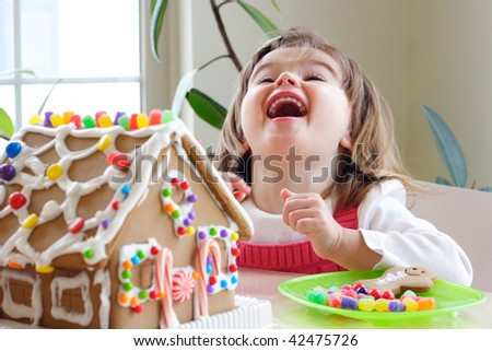 Little girl decorating gingerbread house and laughing - stock photo