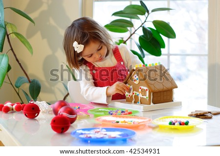 Little girl decorating gingerbread house with colorful candy for Christmas