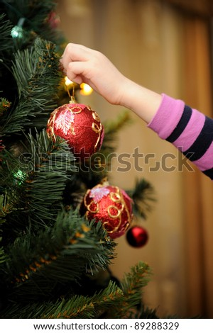 Little girl decorating the Christmas tree (focus on ball) - stock photo
