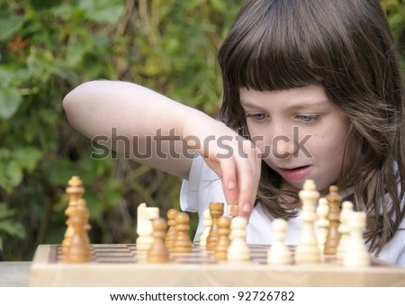Little girl deep in thought as she contemplates her next move in a game of chess.