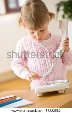 Little girl dial number on phone in lounge holding telephone receiver