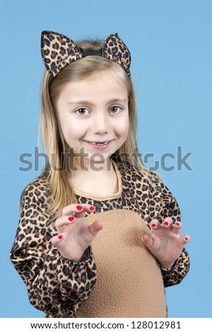 little girl disguised as a leopard, isolated on blue - stock photo