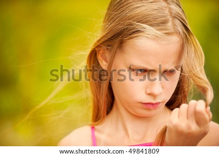 Little girl dissatisfied with brittle hair. - stock photo