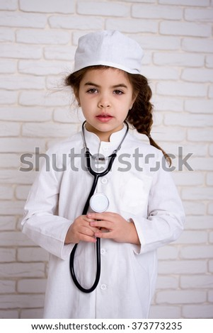 Little girl doctor in the white uniform with stethoscope - stock photo