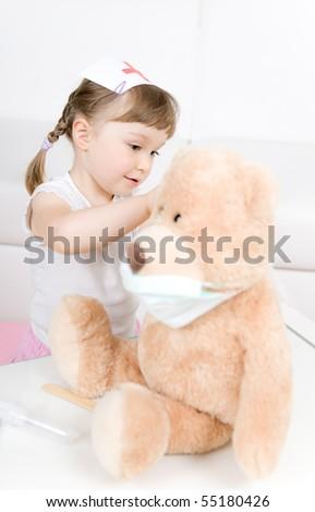little girl doctor with teddy bear - stock photo