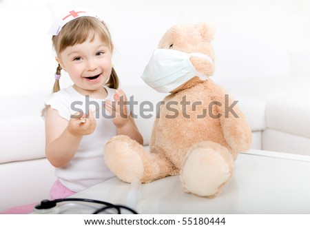 little girl doctor with teddy bear - stock photo