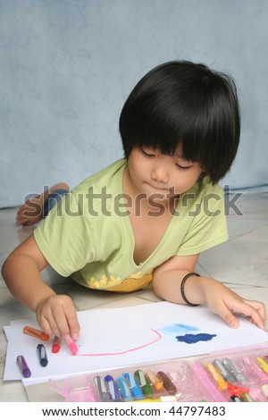 Little girl doing art painting at home alone - stock photo