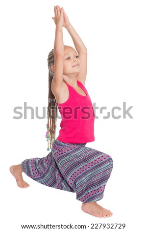 Little girl doing exercises of yoga in Asian attire. Girl is six years old - stock photo