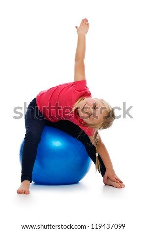 Little girl doing fitness exercise with gym ball. Studio shot. - stock photo
