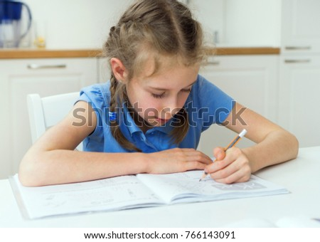 Little girl doing her homework at home.