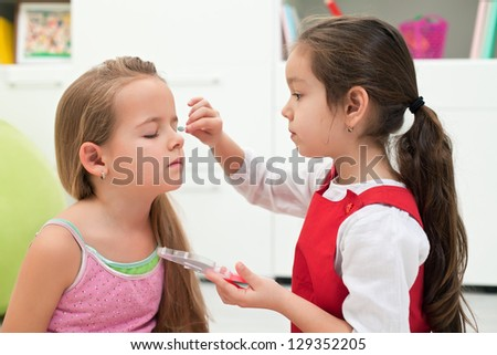 Little girl doing make-up to her girlfriend - stock photo