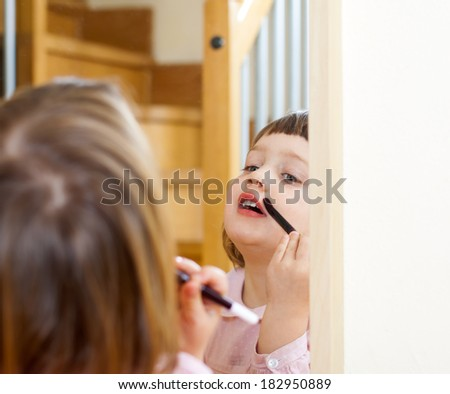 little girl doing makeup  front of  mirror - stock photo