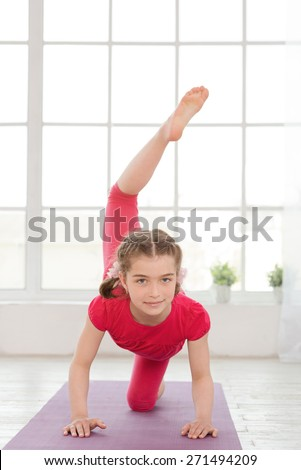 Little girl doing yoga exercise in fitness studio with big windows on background - stock photo
