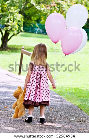 Little girl dragging her teddy bear and carrying a bunch of white and pink balloons.