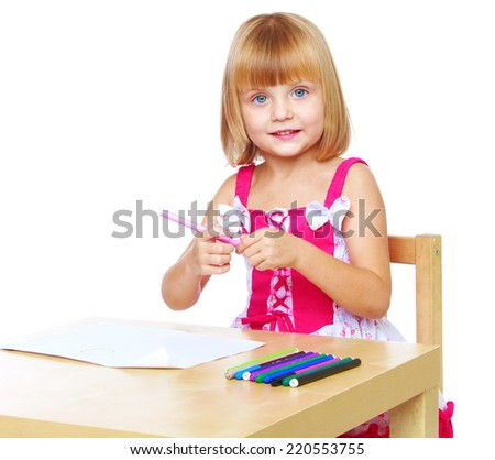 Little girl draw with markers while sitting at table, isolated on white background.The concept of development of the child, the child's upbringing. - stock photo