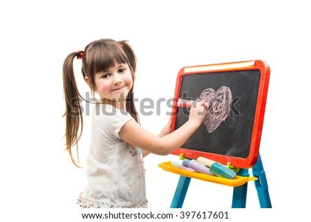 little girl drawing a chalk on a blackboard - stock photo