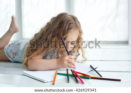 Little girl drawing a picture with color pencils laying on the floor - stock photo