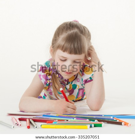 Little girl drawing and lying on the floor, white background - stock photo