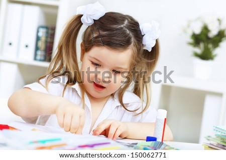 Little girl drawing and studying at home - stock photo