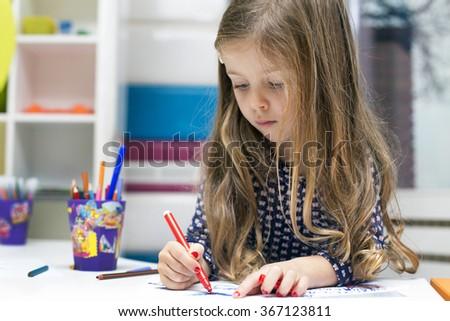 Little girl drawing at playroom - stock photo